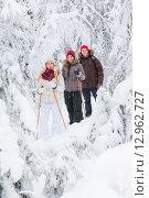 Две девушки и парень на снегоступах прогуливаются в зимнем лесу. Стоковое фото, фотограф Petri Jauhiainen / Фотобанк Лори