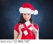 Купить «Composite image of festive brunette holding gift», фото № 12966147, снято 25 июня 2019 г. (c) Wavebreak Media / Фотобанк Лори