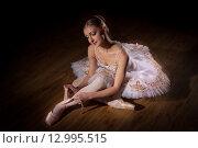 Балерина в белой пачке сидит на полу и завязывает пуанты. Стоковое фото, фотограф Елена Троян / Фотобанк Лори