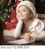 Купить «Задумавшаяся девочка пишет письмо Деду Морозу», фото № 12996515, снято 4 ноября 2012 г. (c) Оксана Гильман / Фотобанк Лори