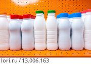 Купить «Пластмассовые бутылки с разноцветными крышками на полке. Молочные продукты», фото № 13006163, снято 9 мая 2012 г. (c) Куликов Константин / Фотобанк Лори
