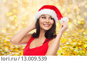 Купить «beautiful woman in santa hat over golden lights», фото № 13009539, снято 25 сентября 2015 г. (c) Syda Productions / Фотобанк Лори