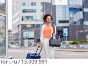 Купить «happy african woman with travel bag and smartphone», фото № 13009991, снято 8 июля 2015 г. (c) Syda Productions / Фотобанк Лори