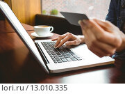 Купить «Student using laptop in cafe to shop online», фото № 13010335, снято 26 июня 2015 г. (c) Wavebreak Media / Фотобанк Лори