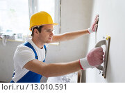 Купить «smiling builder with grinding tool indoors», фото № 13010591, снято 25 сентября 2014 г. (c) Syda Productions / Фотобанк Лори