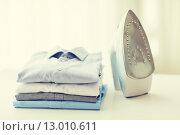 Купить «close up of iron and clothes on table at home», фото № 13010611, снято 13 ноября 2014 г. (c) Syda Productions / Фотобанк Лори