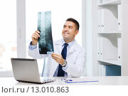 Купить «smiling male doctor in white coat looking at x-ray», фото № 13010863, снято 3 февраля 2015 г. (c) Syda Productions / Фотобанк Лори