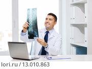 Купить «smiling male doctor in white coat looking at x-ray», фото № 13010863, снято 3 февраля 2015 г. (c) Syda Productions / Фотобанк Лори