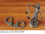 Купить «Фигурка Фемиды и наручники на деревянном столе», фото № 13011919, снято 29 октября 2015 г. (c) Денис Ларкин / Фотобанк Лори