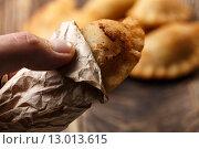 Купить «Male hand holding fried colombian empanada. Savory stuffed patties also known as pastel,pate or pirozhki», фото № 13013615, снято 21 апреля 2019 г. (c) PantherMedia / Фотобанк Лори