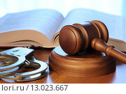 Купить «Судейский молоток, уголовный кодекс и наручники лежат на столе», фото № 13023667, снято 30 октября 2015 г. (c) Денис Ларкин / Фотобанк Лори