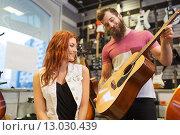 Купить «couple of musicians with guitar at music store», фото № 13030439, снято 11 декабря 2014 г. (c) Syda Productions / Фотобанк Лори