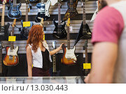 Купить «assistant showing customer guitar at music store», фото № 13030443, снято 11 декабря 2014 г. (c) Syda Productions / Фотобанк Лори