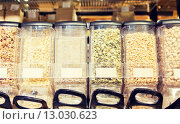 Купить «row of jars with nuts and seeds at grocery store», фото № 13030623, снято 20 декабря 2014 г. (c) Syda Productions / Фотобанк Лори