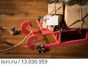 Купить «close up of christmas gifts with note on sleigh», фото № 13030959, снято 7 октября 2015 г. (c) Syda Productions / Фотобанк Лори