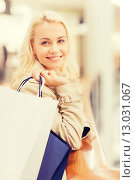 Купить «happy young woman with shopping bags in mall», фото № 13031067, снято 3 ноября 2014 г. (c) Syda Productions / Фотобанк Лори