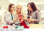 Купить «happy women with smartphones and shopping bags», фото № 13032851, снято 3 ноября 2014 г. (c) Syda Productions / Фотобанк Лори