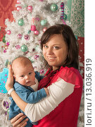 Купить «Мама с младенцем на фоне новогодней елки», фото № 13036919, снято 11 января 2014 г. (c) Юлия Бабкина / Фотобанк Лори