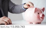 Купить «close up of man putting money into piggy bank», видеоролик № 13050743, снято 12 апреля 2015 г. (c) Syda Productions / Фотобанк Лори
