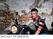 Купить «Tough guy with his bike in front of a brick wall», фото № 13059615, снято 25 июня 2018 г. (c) PantherMedia / Фотобанк Лори