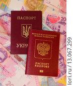 Купить «Украинский и российский заграничные паспорта на фоне украинских денег», фото № 13067299, снято 15 ноября 2015 г. (c) Ивашков Александр / Фотобанк Лори