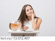 Девушка задумалась записывая в блокноте желания для исполнения золотой рыбкой. Стоковое фото, фотограф Иванов Алексей / Фотобанк Лори