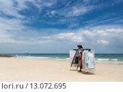 Торговец одеждой идет по пляжу на фоне голубого неба. Редакционное фото, фотограф Анна Королева / Фотобанк Лори