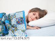 Купить «Улыбающийся ребёнок, лежащий в постели под лоскутным одеялом», фото № 13074971, снято 15 ноября 2015 г. (c) Юлия Кузнецова / Фотобанк Лори