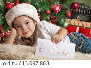 Купить «Маленькая девочка держит письмо для Санты», фото № 13097863, снято 2 ноября 2013 г. (c) Оксана Гильман / Фотобанк Лори