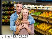 Купить «Smiling couple hugging in fruit aisle», фото № 13103259, снято 14 апреля 2015 г. (c) Wavebreak Media / Фотобанк Лори