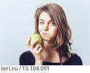 Купить «Beautiful young woman bites a green apple on a gray background», фото № 13104091, снято 23 апреля 2015 г. (c) Ingram Publishing / Фотобанк Лори