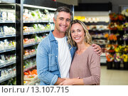 Купить «Smiling couple hugging in fruit aisle», фото № 13107715, снято 14 апреля 2015 г. (c) Wavebreak Media / Фотобанк Лори