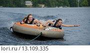 Купить «Two girls lying on an inflatable raft floating in a lake», фото № 13109335, снято 5 июля 2014 г. (c) Ingram Publishing / Фотобанк Лори
