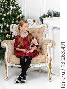 Девочка в кресле с игрушкой в новогоднем белом интерьере. Стоковое фото, фотограф Максим Тимофеев / Фотобанк Лори