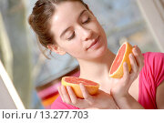 Купить «Woman holding fruit  Young woman holding half a pink grapefruit in both hands», фото № 13277703, снято 28 февраля 2009 г. (c) age Fotostock / Фотобанк Лори