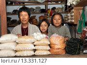 Gemüsehändlerin mit ihren zwei Töchtern hinter Tüten mit Reis im Verkaufsstand auf dem Gemüsemarkt in Lobesa, Bhutan / Female vegetable seller with her... Стоковое фото, фотограф Zoonar/GFC Collectio / age Fotostock / Фотобанк Лори