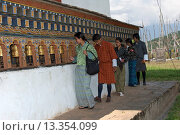 Junge Bhutanese in traditioneller Kleidung an den Gebetsmühlen im Fruchtbarkeitstempel Chimi Lhakhang, Lobesa, Bhutan / Young Bhutanese in traditional... Стоковое фото, фотограф Zoonar/Georg / age Fotostock / Фотобанк Лори