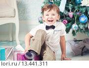 Купить «Веселый мальчик в белой рубашке с бабочкой сидит на фоне новогодней елки и смеется», фото № 13441311, снято 26 декабря 2013 г. (c) Вероника Галкина / Фотобанк Лори