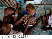 Купить «A girl feeds his younger brother by rice in the slum of Cité Soleil, Port-au-Prince, Haiti, 22 July 2008  Rice is a basic source of nutrition for all Haitians...», фото № 13462899, снято 22 июля 2008 г. (c) age Fotostock / Фотобанк Лори