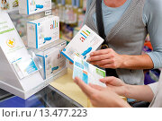 Купить «Woman buying Alli medicine in pharmacy. Alli is a half_dose version of the diet drug Xenical Orlistat produced by GlaxoSmithKline GSK. First anti_obesity...», фото № 13477223, снято 26 мая 2019 г. (c) age Fotostock / Фотобанк Лори
