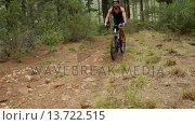 Купить «Man biking through a forest », видеоролик № 13722515, снято 15 октября 2019 г. (c) Wavebreak Media / Фотобанк Лори