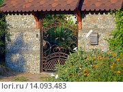 Купить «Кованая калитка в каменном заборе под железным навесом», фото № 14093483, снято 17 августа 2015 г. (c) Александр Замараев / Фотобанк Лори