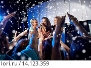 Купить «happy young women singing karaoke in night club», фото № 14123359, снято 20 октября 2014 г. (c) Syda Productions / Фотобанк Лори