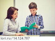 Купить «school boy with notebook and teacher in classroom», фото № 14124787, снято 15 ноября 2014 г. (c) Syda Productions / Фотобанк Лори