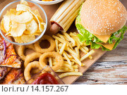 Купить «close up of fast food snacks on wooden table», фото № 14157267, снято 21 мая 2015 г. (c) Syda Productions / Фотобанк Лори
