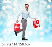 Купить «smiling man walking with red shopping bag», фото № 14158607, снято 3 октября 2015 г. (c) Syda Productions / Фотобанк Лори