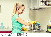 Купить «happy woman cleaning tap at home kitchen», фото № 14159415, снято 25 января 2015 г. (c) Syda Productions / Фотобанк Лори