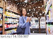 Купить «happy woman with notepad in grocery store», фото № 14159907, снято 20 декабря 2014 г. (c) Syda Productions / Фотобанк Лори