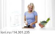 Купить «smiling young woman chopping eggplant at home», видеоролик № 14301235, снято 2 мая 2015 г. (c) Syda Productions / Фотобанк Лори