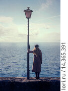 Купить «a woman in a pink coat is standing next to a lantern at the sea.», фото № 14365391, снято 1 декабря 2013 г. (c) age Fotostock / Фотобанк Лори